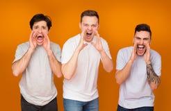 Mensen die luid over oranje studioachtergrond gillen stock foto's