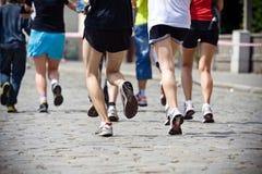 Mensen die in marathon op stadsstraat lopen Stock Foto's