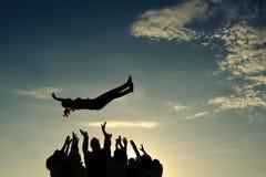 Mensen die meisje in de lucht werpen Stock Foto's