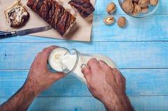 Mensen die melk gieten in een glas op blauwe oppervlakteclose-up Royalty-vrije Stock Afbeelding