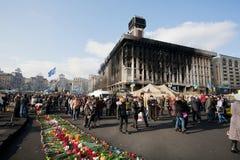 Mensen die met bloemen de voorbij gebrande bouw lopen Royalty-vrije Stock Foto's