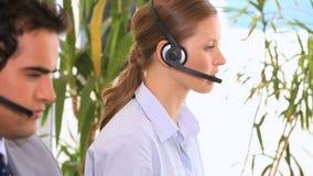 Mensen die met hoofdtelefoons werken stock video