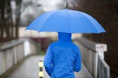 Mensen die met paraplu in de regen lopen Stock Foto