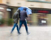 Mensen die met paraplu onderaan de straat op regenachtige dag lopen royalty-vrije stock foto