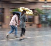 Mensen die met paraplu onderaan de straat op regenachtige dag lopen stock foto's