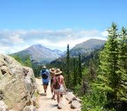 Mensen die met rugzakken op de zomervakantie wandelen Royalty-vrije Stock Afbeeldingen