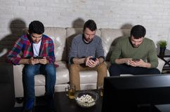 Mensen die Mobiele Telefoons met behulp van terwijl het Letten van op Televisie royalty-vrije stock foto