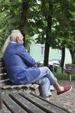 Mensen die, modieuze kleren, parkbank in modern CIT zitten stock foto