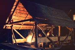 Mensen die naast brand bij nacht in houten zitten stock foto's