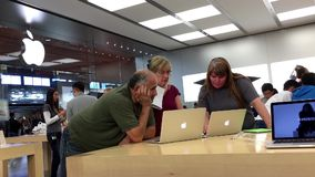 Mensen die nieuwe Macbook binnen Apple-opslag kopen stock videobeelden