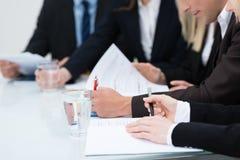 Mensen die nota's in een vergadering nemen Royalty-vrije Stock Foto
