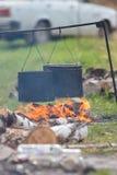 Mensen die omhoog water in de metaalemmers verwarmen die een vuur gebruiken Emmers die op de dwarsbalk hangen royalty-vrije stock foto's