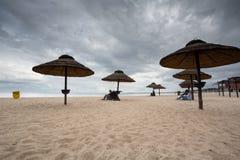 Mensen die onder hout gemaakte paraplu's op het strand van Sopot zitten Stock Foto's