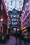Mensen die onder lightbulblichten lopen in Carnaby-Straat, Londen, het UK Royalty-vrije Stock Afbeeldingen