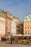 Mensen die onder paraplu's bij het centrale vierkant in Riga zitten stock afbeeldingen