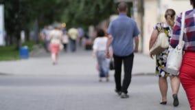 Mensen die onderaan de straat in de avond, mooi licht bij zonsondergang lopen De foto wordt met opzet gemaakt uit nadruk, nr stock video
