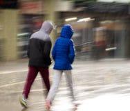 Mensen die onderaan de straat op regenachtige dag lopen royalty-vrije stock fotografie