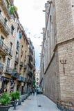Mensen die onderaan een steeg/een smalle straat op een gebied van zowel woon als commerciële eigendommen in Barcelona lopen royalty-vrije stock fotografie