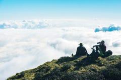 Mensen die op Bergklip rusten die van de hoogste Horizon van de wolkenhemel genieten Royalty-vrije Stock Foto's