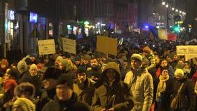 Mensen die op de avondstraat lopen, menigten met aanplakbiljetten stock videobeelden