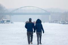 Mensen die op de bevroren rivier Tamis in Pancevo, Servië lopen toe te schrijven aan een uitzonderlijk koud weer over de Balkan Stock Fotografie