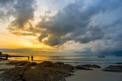 Mensen die op de zon in de ochtend bij het strand wanneer letten Stock Afbeeldingen