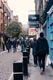 Mensen die op een bestrating in Covent-Tuin, Londen, het UK lopen Stock Foto