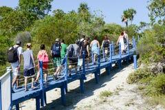 Mensen die op een brug lopen om het strand te bereiken Royalty-vrije Stock Foto's