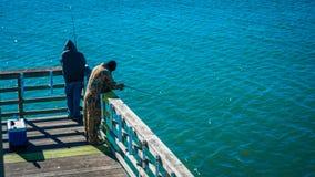 Mensen die op een pijler bij de kust vissen royalty-vrije stock foto's