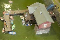 Mensen die op een ponton met boten in een miniatuurwereldopstelling baden stock foto