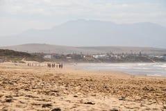 Mensen die op een strand in Mossel-Baai, Zuid-Afrika lopen Royalty-vrije Stock Afbeeldingen
