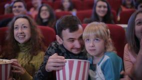 Mensen die op film in bioskoop en het lachen letten stock video