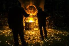 Mensen die op fonkelend smeltend staal in oven van gieterij letten stock fotografie