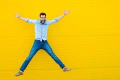 Mensen die op gele achtergrond springen royalty-vrije stock afbeelding