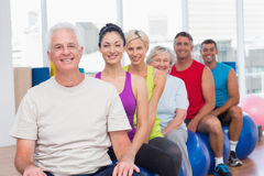 Mensen die op geschiktheidsballen ontspannen in gymnastiekklasse Stock Foto's
