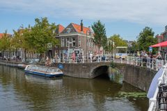 Mensen die op het mooie historische oude kanaal in het centrum van Delft, Nederland letten stock foto