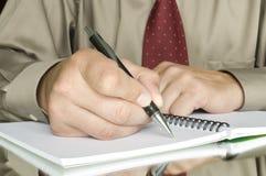 Mensen die op het notitieboekje schrijven Stock Fotografie