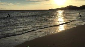 Mensen die op het strand bij zonsopgang genieten van stock video