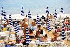 Mensen die op het strand in Nice, Frankrijk zonnebaden Stock Afbeeldingen