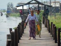Mensen die op houten brug in Myanmar lopen Royalty-vrije Stock Foto