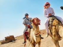 Mensen die op kamelen reizen Stock Foto