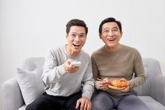Mensen die op laag het letten op film op televisie samen thuis zitten royalty-vrije stock fotografie