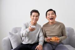 Mensen die op laag het letten op film op televisie samen thuis zitten stock foto's