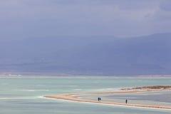 Mensen die op landtong op stormachtige dag bij Dode Overzees lopen Royalty-vrije Stock Afbeeldingen