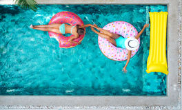 Mensen die op opblaasbare ring in pool ontspannen royalty-vrije stock foto