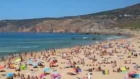 Mensen die op overvol strand, golven zonnebaden die op kust, de zonnige zomer rollen stock footage