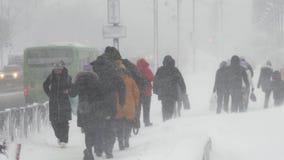 Mensen die op stad tijdens zware sneeuwval lopen, Vreedzame sneeuwcycloon stock footage