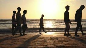 Mensen die op strand bij zonsondergang lopen stock video