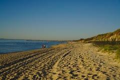 Mensen die op strand met pijler, blauw water en blauwe hemel op achtergrond lopen royalty-vrije stock afbeelding