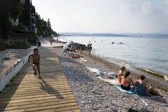 Mensen die op strand op 30 Juli 2016 in Desenzano del Garda, Italië zonnebaden Stock Foto